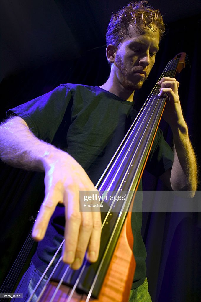 medium shot of a young adult male as he plays his electric bass while on stage : Stockfoto