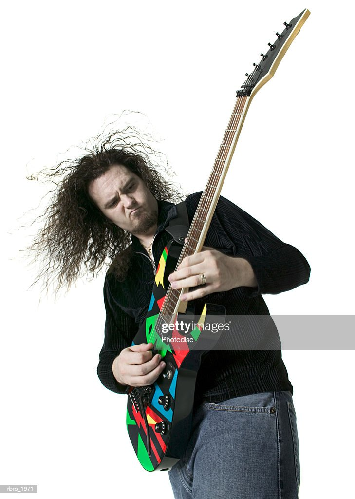 medium shot of a young adult male as he plays his electric guitar : Stockfoto
