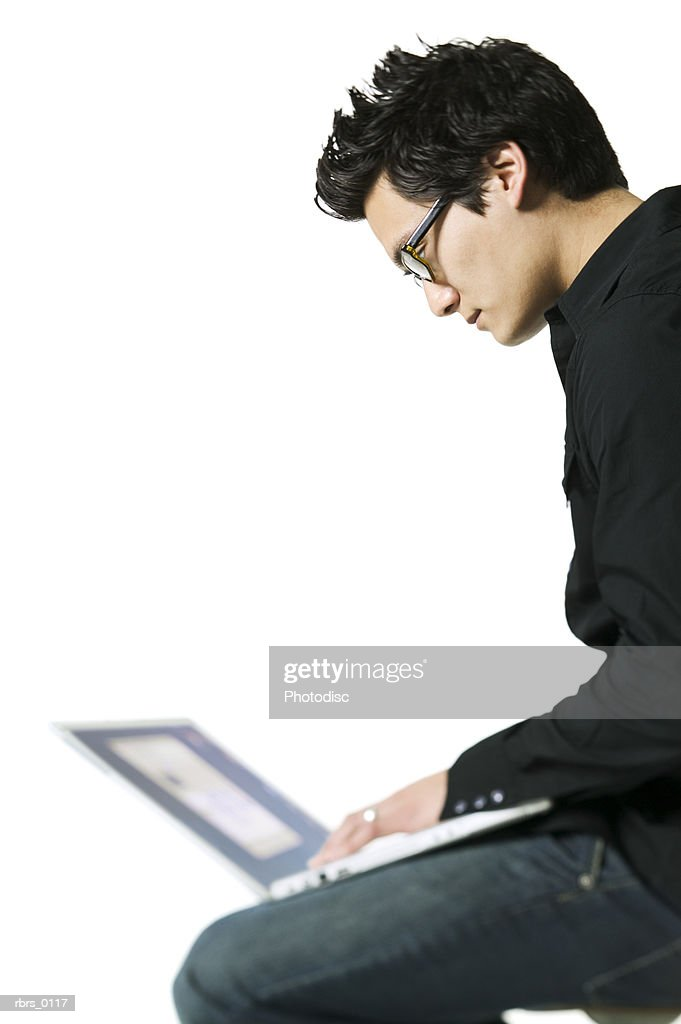 medium shot of a young adult male as he sits and works on his laptop computer : Foto de stock