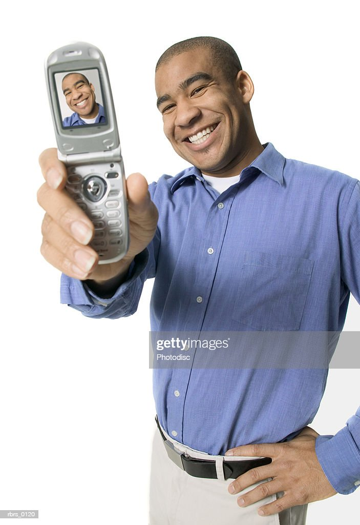 medium shot of a young adult male as he smiles for his camera phone : Foto de stock