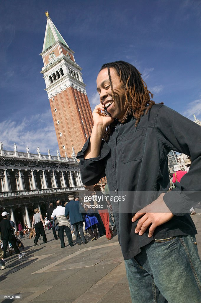 medium shot of a young adult male as he talks on his cell phone while in venice : Foto de stock