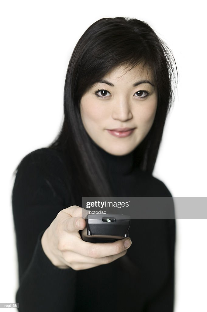 medium shot of a young adult woman as she uses a television remote control : Stockfoto