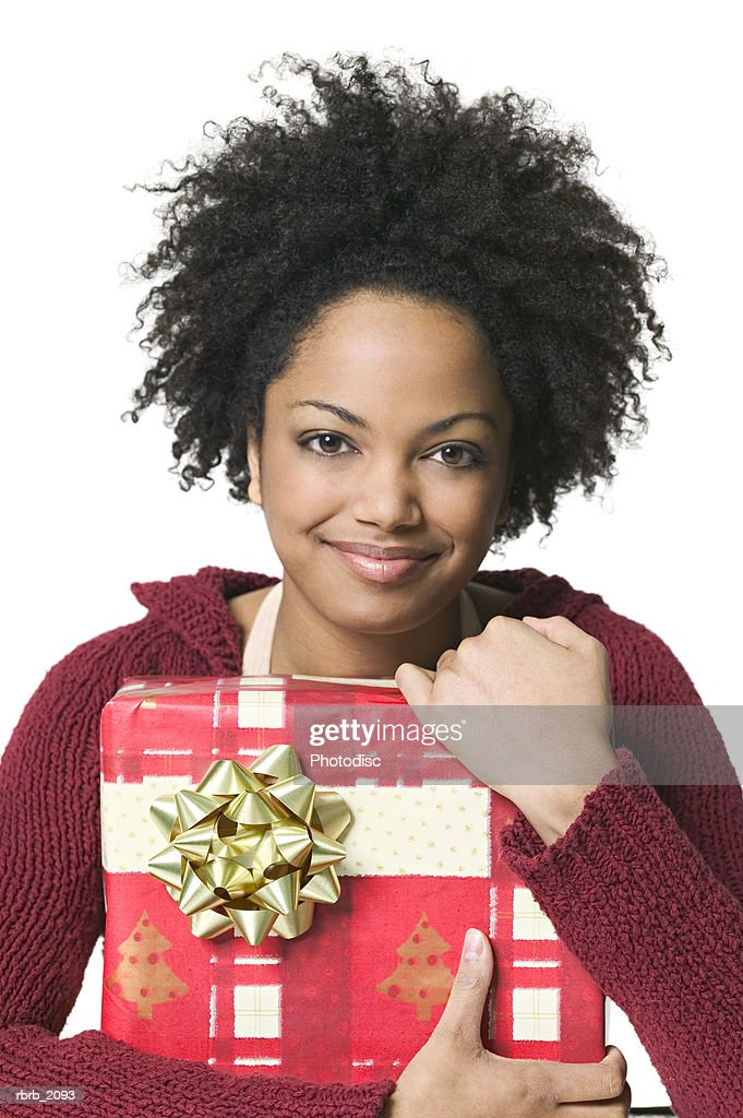 medium shot of a young adult woman as she wraps her arms around a christmas gift : Stockfoto