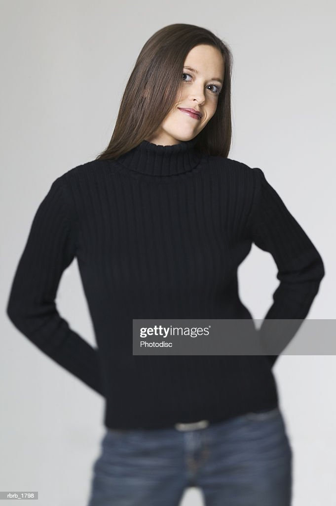 medium shot of a young adult woman in a black sweater as she puts her hands on her hips and smiles : ストックフォト