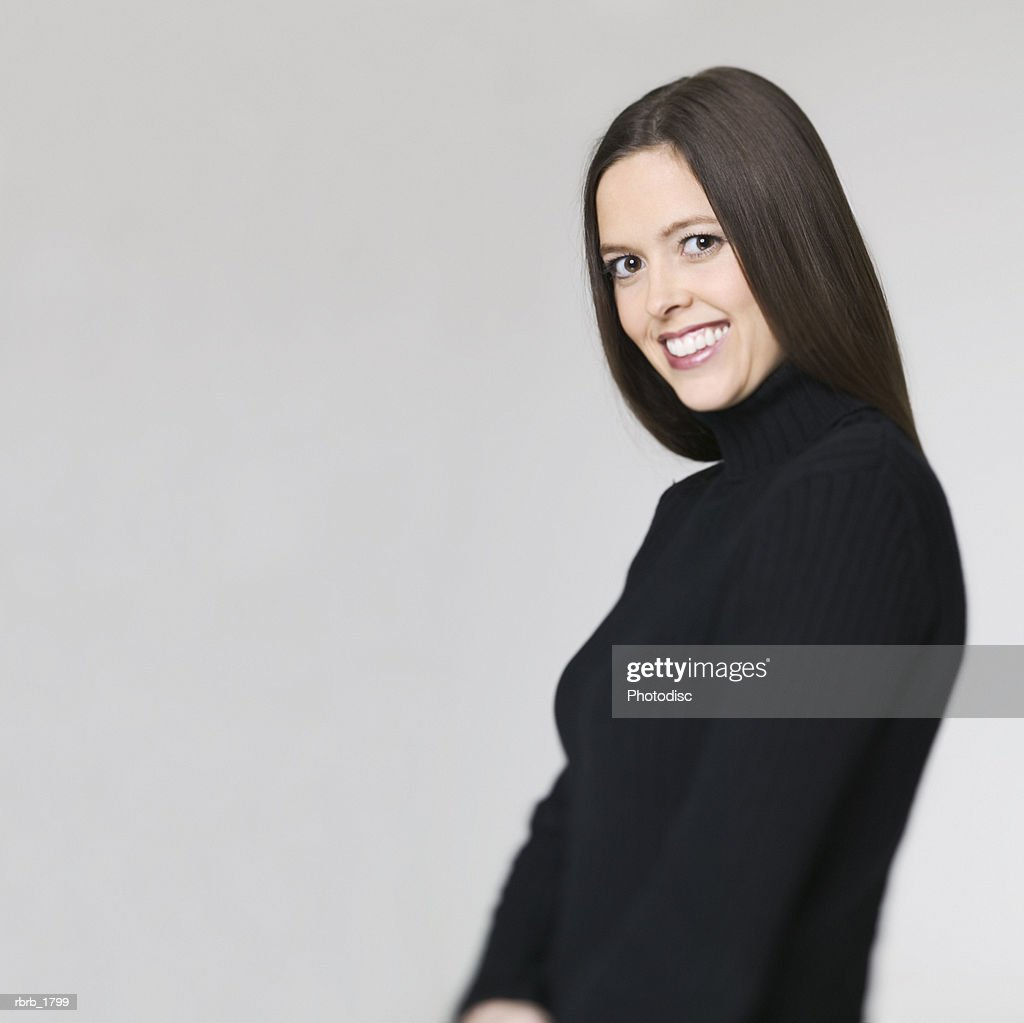 medium shot of a young adult woman in a black sweater as she turns and smiles : Stockfoto