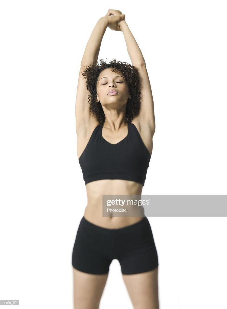 medium shot of a young adult woman in a black workout outfit as she stretches out : Stockfoto