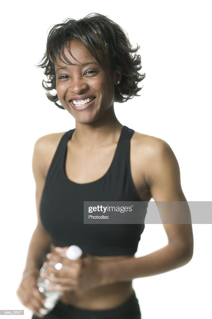 medium shot of a young adult woman in a black workout outfit as she holds her water and smiles : Stockfoto