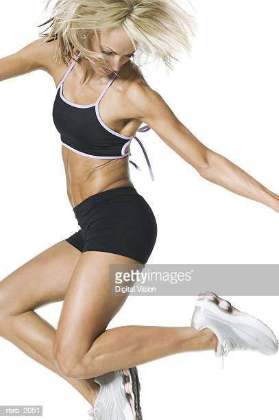 medium shot of a young adult woman in a black workout outfit as she skips up in the air - running shorts stock pictures, royalty-free photos & images