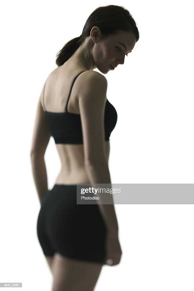 medium shot of a young adult woman in a black workout outfit as she glances downward : Stockfoto