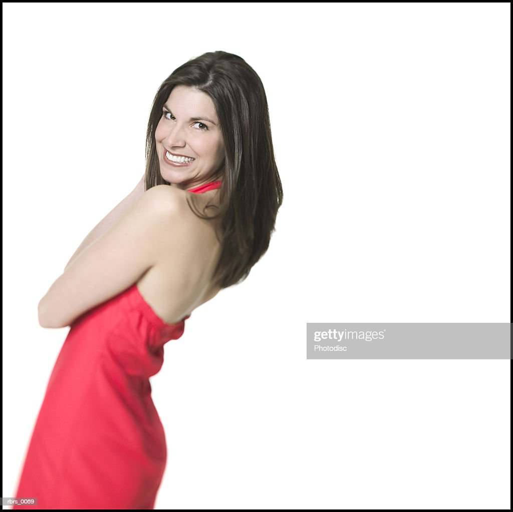 medium shot of a young adult woman in a red dress as she turns and smiles at the camera : Foto de stock