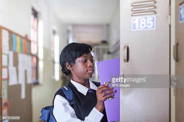 Medium shot of African female student placing file in locker in hallway, Cape Town, South Africa