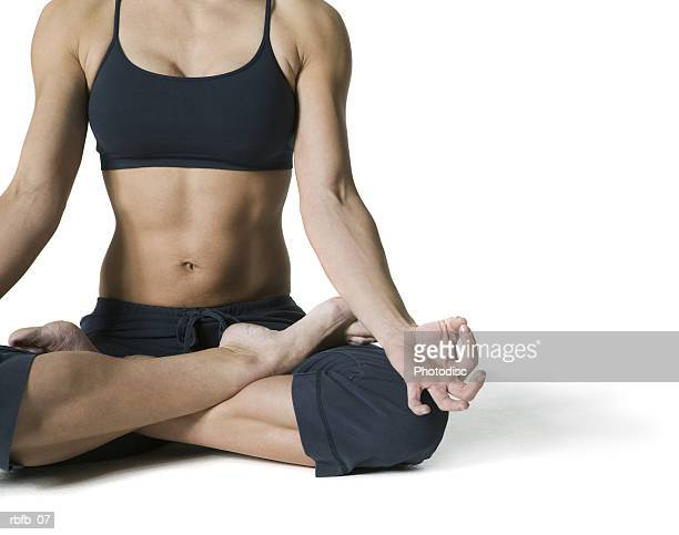 medium shot of an adult woman in a workout outfit as she sits and does yoga