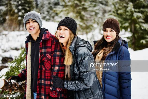medium shot of family laughing while cutting christmas tree in snow on winter afternoon - embellished jacket stock pictures, royalty-free photos & images