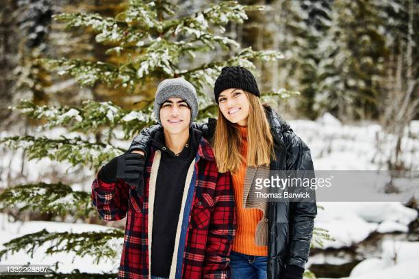 medium shot of smiling teenage brother and sister standing in forest while cutting christmas tree on winter afternoon - embellished jacket stock pictures, royalty-free photos & images