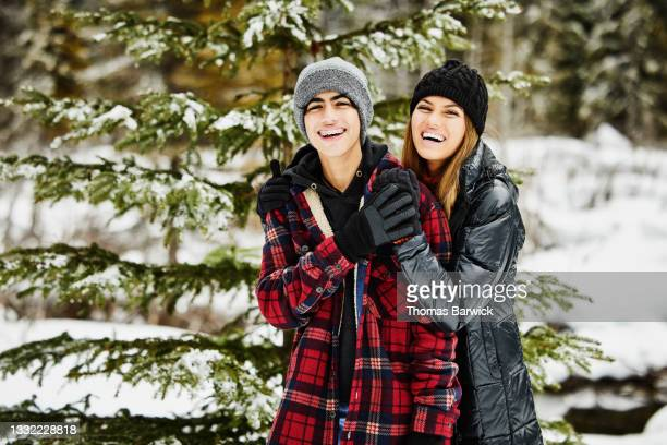 medium shot of teenage brother and sister laughing while cutting christmas tree in forest on winter afternoon - embellished jacket stock pictures, royalty-free photos & images