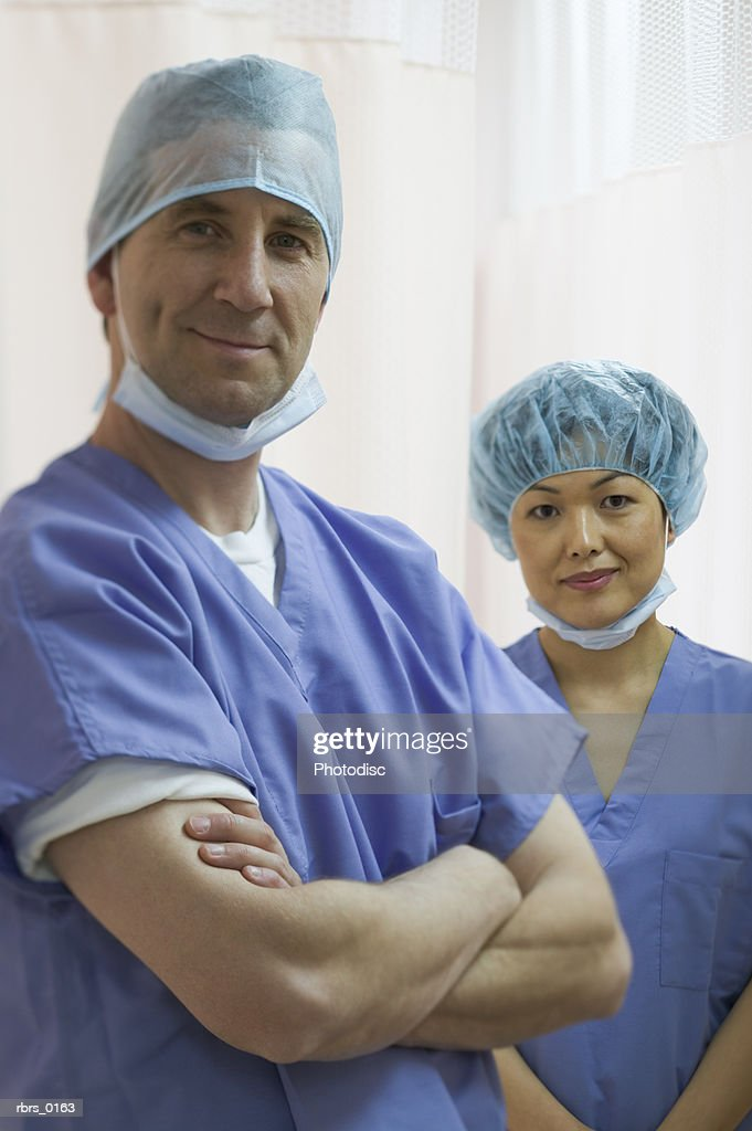 medium shot of two adult medical surgeons as the pose in front of a curtain : Foto de stock