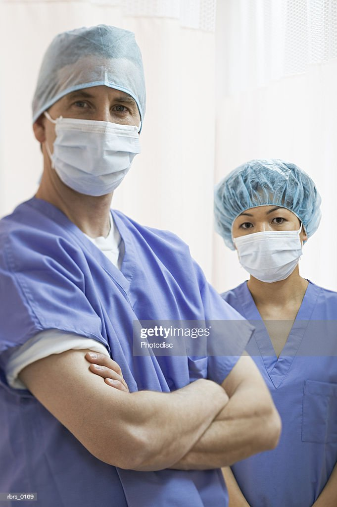 medium shot of two medical surgeons in blue scrubs and masks as they look at the camera : Foto de stock