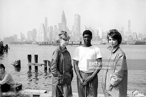 Medium shot of two young Italian models in raincoats named Flora and Lucia standing on the bank of the Hudson river together with a young black man...