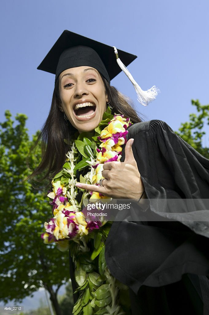 medium shot of young adult female in cap and gown with floral lei as she celebrates her graduation : Foto de stock