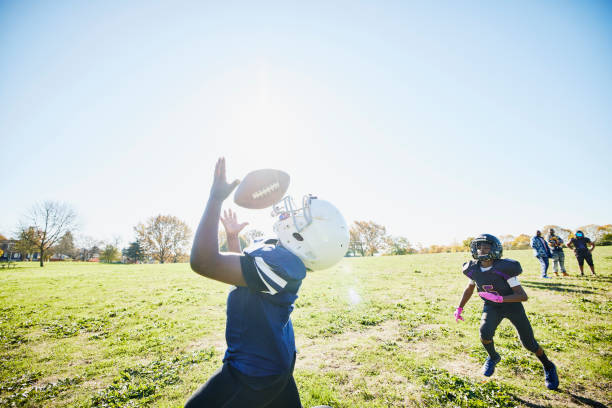 Medium shot of young football player catching pass during practice on fall afternoon