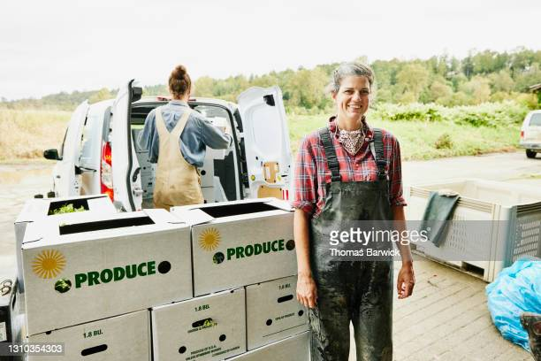 medium shot portrait of smiling female farmer standing next to freshly packed csa boxes - washington state stock pictures, royalty-free photos & images