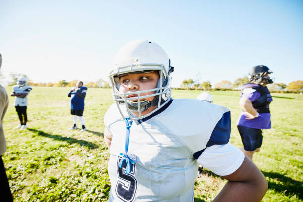 Medium shot portrait of young football player standing on field during practice on fall afternoon