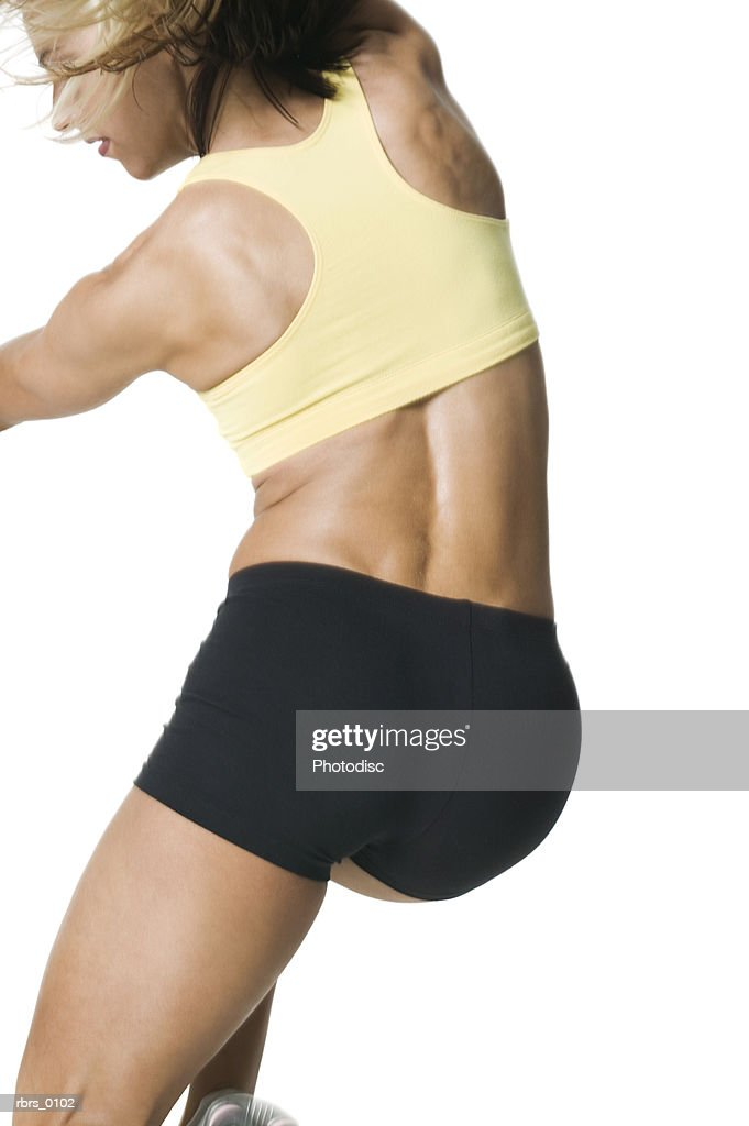 medium shot rear view of a young adult woman in a workout outfit as she jumps : Foto de stock