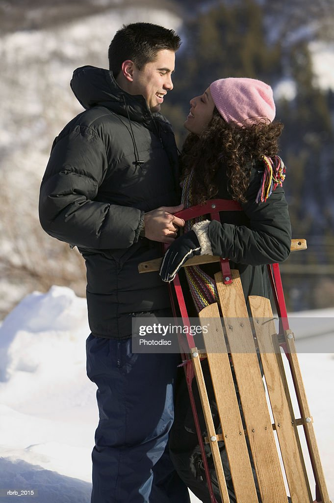 medium wide shot of a young adult couple as they hug while out sledding : Stockfoto
