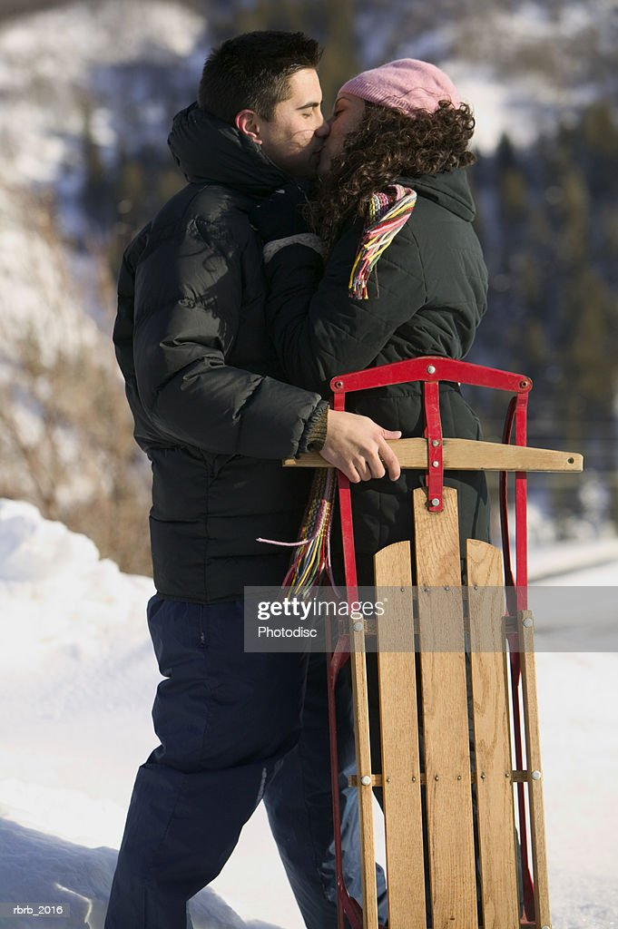 medium wide shot of a young adult couple as they passionately kiss while out sledding : Stock Photo