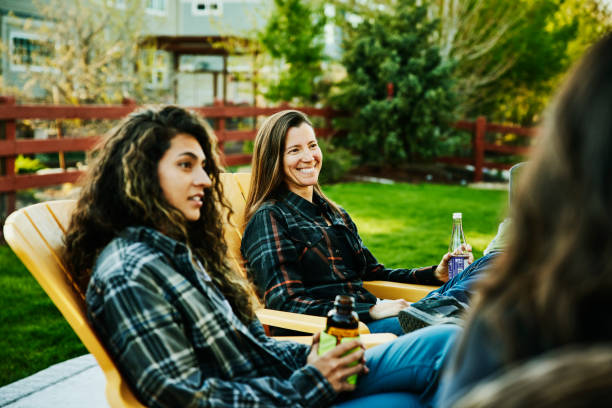 Medium wide shot of smiling female friends sharing drinks in backyard
