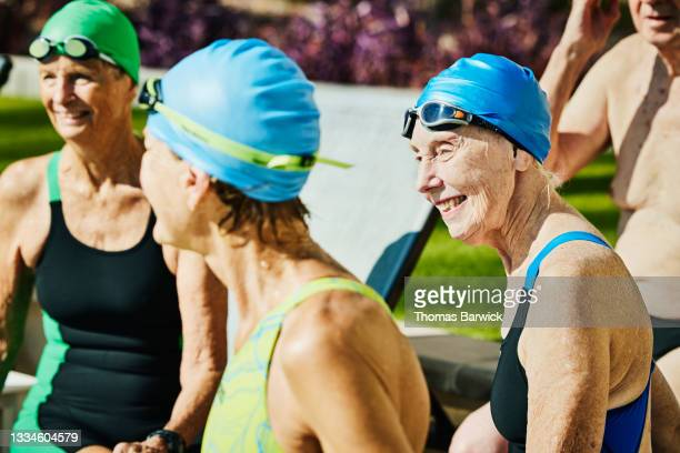 medium wide shot of smiling senior swimmers in discussion while hanging out on pool deck after morning workout - medium group of people photos et images de collection