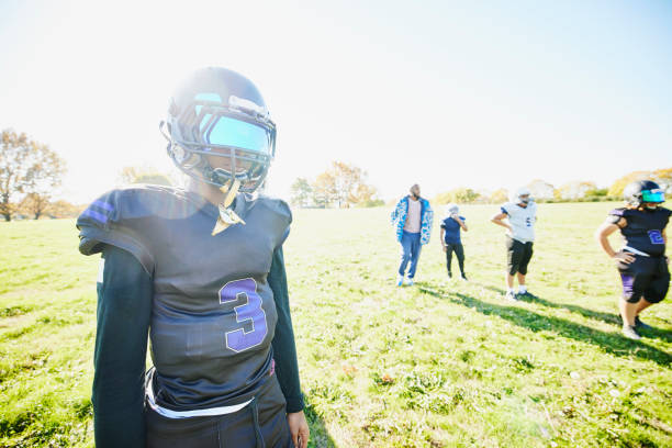 Medium wide shot of young football player standing on field during practice on fall afternoon