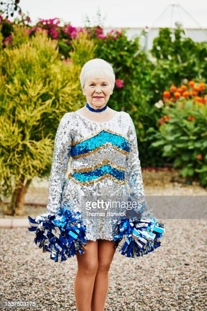 medium wide shot portrait of smiling senior female cheerleader in backyard garden - fringe dress stock pictures, royalty-free photos & images