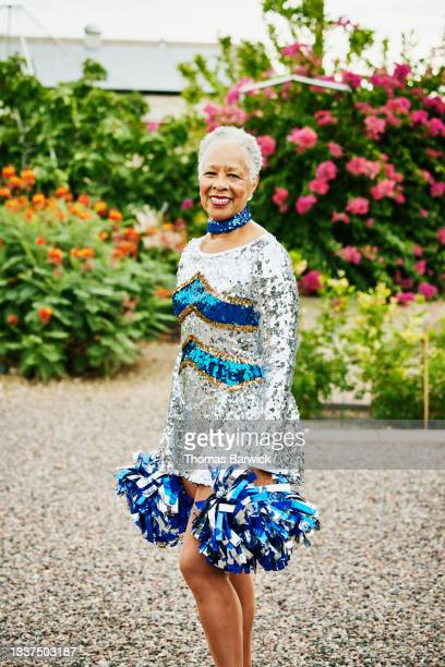 medium wide shot portrait of smiling senior female cheerleader in backyard garden - mini dress stock pictures, royalty-free photos & images