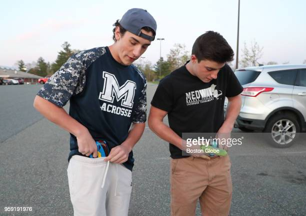 Medway High School seniors Joey Bevilacqua left and Rob DiGregorio put their squirt guns in their waistbands in the school parking lot before heading...