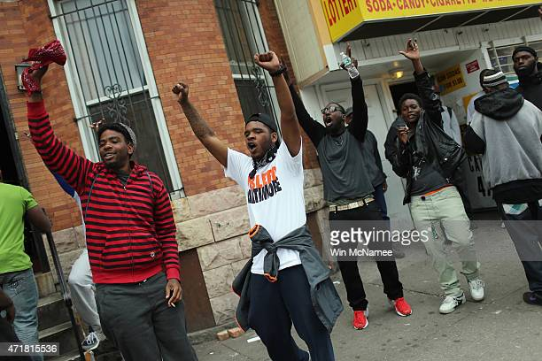 Meech Johnson raises his hands in the air along with others after Baltimore authorities released a report on the death of Freddie Gray on May 1 2015...