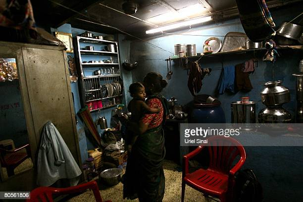 Meena Kamaniqan holds her grendson at their one room home at the Dharavi slum said to be 'Asia's largest slum' April 2008 in Mumbai India A city...