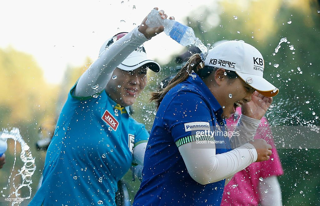 Meena Lee (L) sprays water on Inbee Park of South Korea after Park defeated Brittany Lincicome on the first playoff hole during the Wegmans LPGA Championship at Monroe Golf Club on August 17, 2014 in Pittsford, New York.