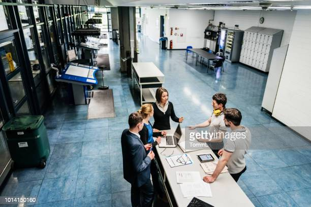 meeting between engineers on factory floor - complexity stock pictures, royalty-free photos & images