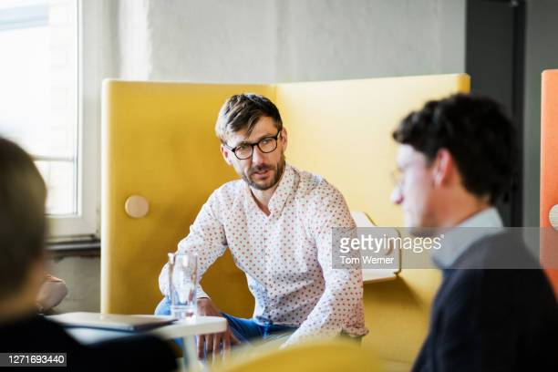 meeting between office staff in modern workspace - yellow stock pictures, royalty-free photos & images