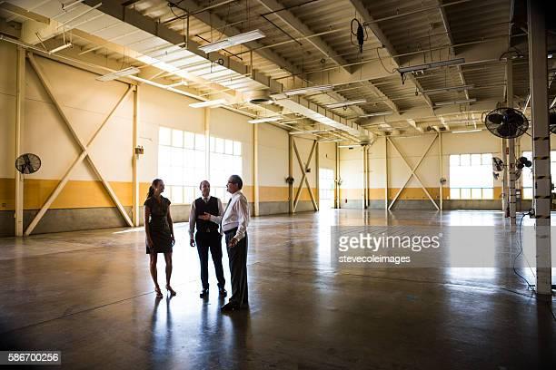 meeting in empty office warehouse - mercado espacio de comercio fotografías e imágenes de stock