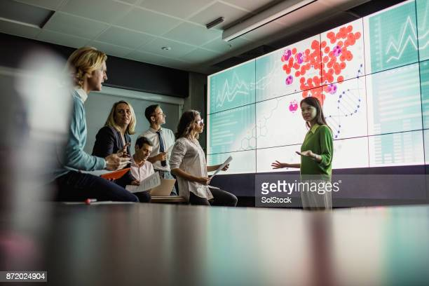 meeting in front of a large display screen - data stock pictures, royalty-free photos & images