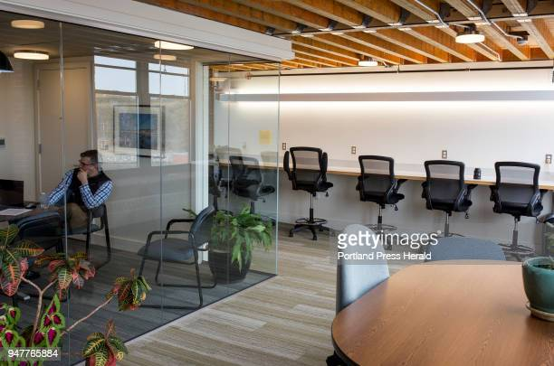 A meeting in glass conference room at left and individual work stations for guests or employees that need a change of scenery during the work day at...