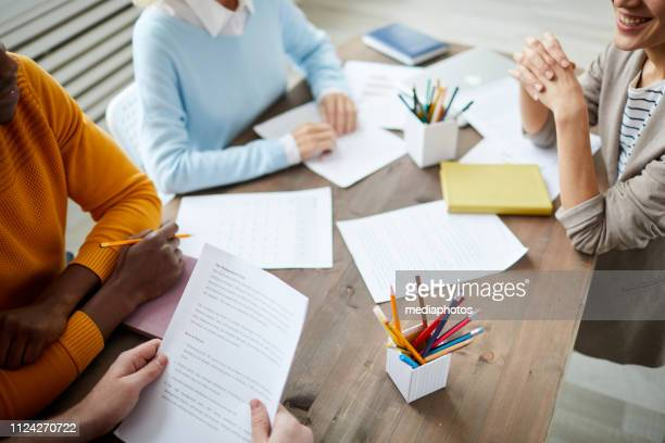 Meeting of creative team: close-up of young business people sitting at table with papers and discussing deal while analyzing contract together