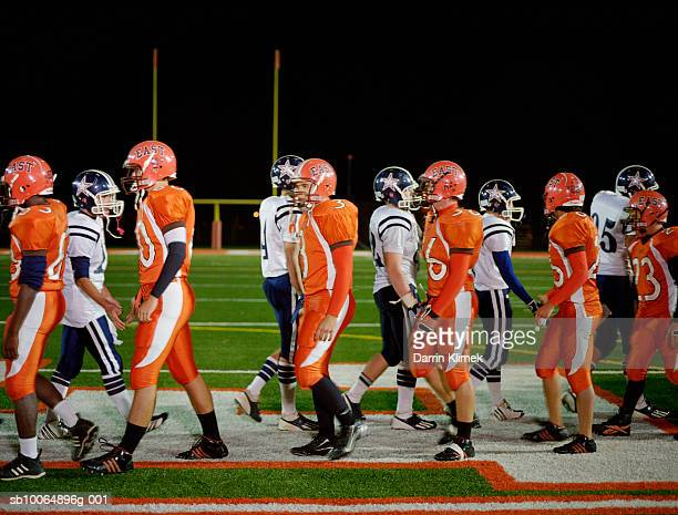 meeting of teams of american football in field, side view - american football team stock pictures, royalty-free photos & images