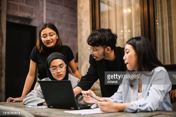 meeting of young professionals in a co-working space - indonesia stock pictures, royalty-free photos & images