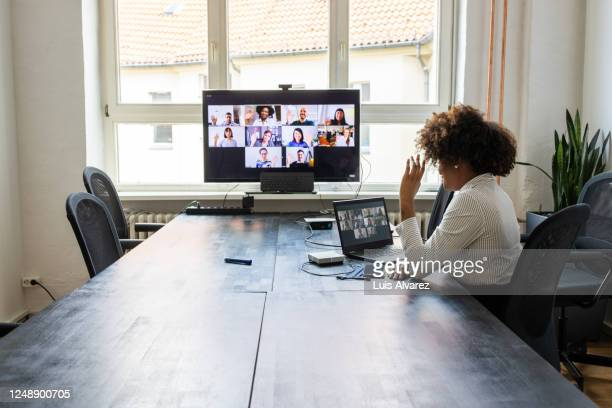 meeting over a video call in office post pandemic - employee engagement stock pictures, royalty-free photos & images