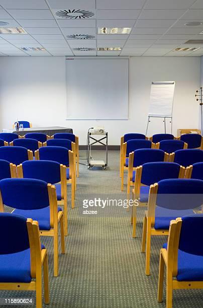 Meetingraum mit blauen Stühlen Projektor und eine Leinwand stehen