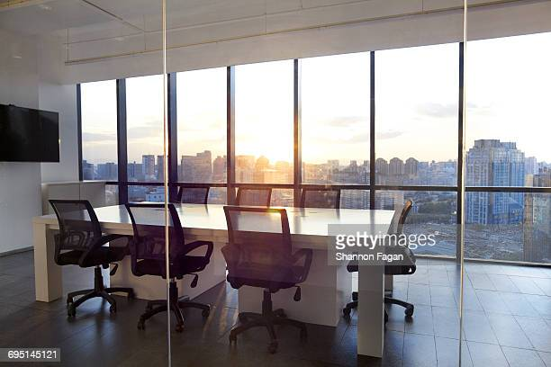 Meeting room with glass wall cityscape and sunset