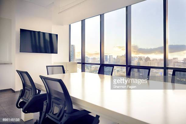 meeting room with view of cityscape sunset - konferenzraum stock-fotos und bilder